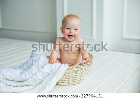 smiling baby girl sitting in basket with white blanket in white interrior - stock photo
