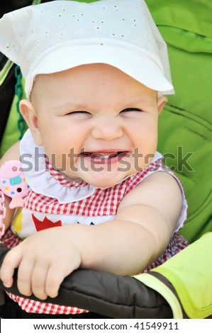 smiling baby girl sitting in the stroller