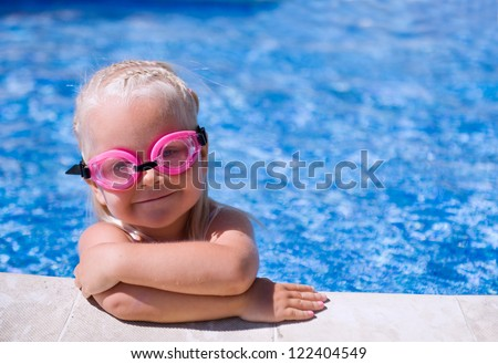 Smiling baby girl  wearing swimming glasses in swimming pool - stock photo