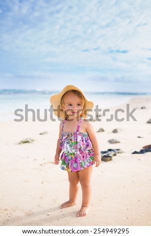 Smiling baby girl wearing swimsuit and hat on a tropical beach