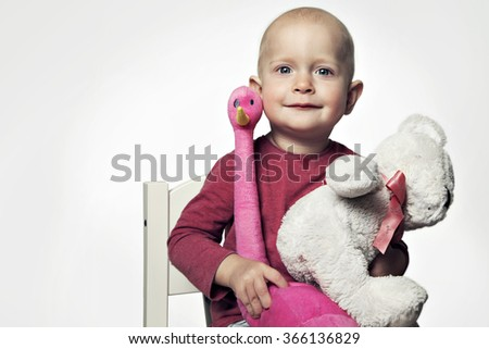 Smiling baby girl 1-2 year old having fun on white. Looking at camera with toys - stock photo