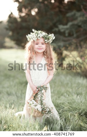 Smiling baby girl 3-4 year old holding basket with flowers outdoors. Wearing floral wreath. Looking at camera. Childhood. Elegance. - stock photo