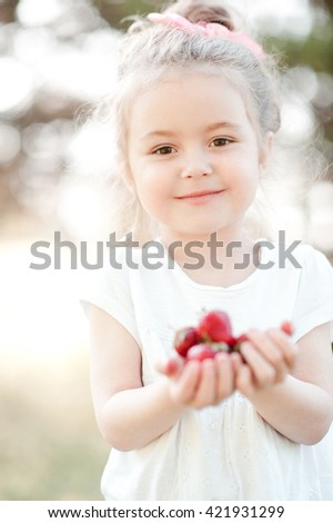 Smiling baby girl 3-4 year old holding strawberries outdoors closeup. Looking at camera. Childhood. Healthy eating. - stock photo