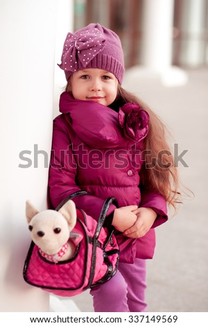 Smiling baby girl 3-4 year old holding toy pet in bag outdoors. Looking at camera. Wearing trendy winter jacket. Childhood.  - stock photo