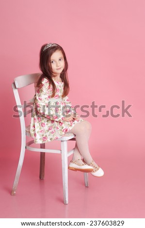 Smiling baby girl 4-5 year old posing in studio over pink. Sitting on chair. Wearing trendy floral dress.  - stock photo