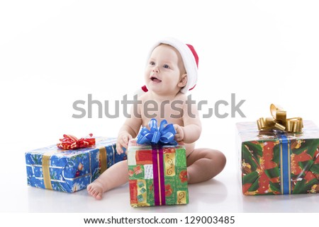Smiling baby in a cap of Santa Claus sitting on the floor with gifts. On a white background with reflection - stock photo
