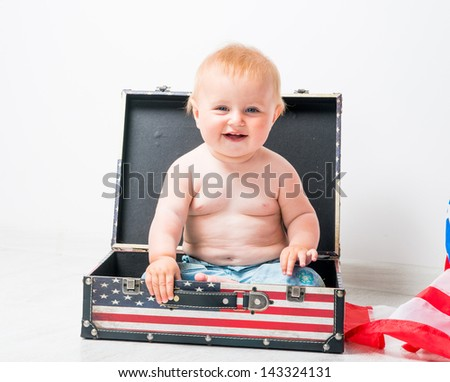 smiling baby in a suitcase with American flag - stock photo