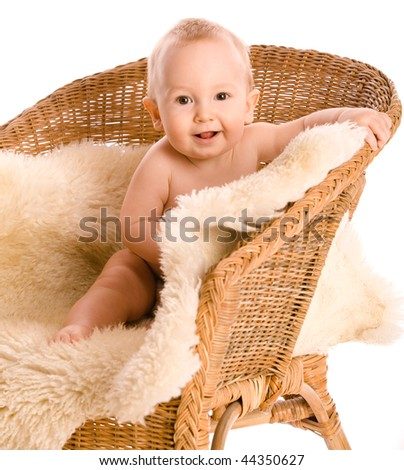 Smiling baby in armchair isolated on white - stock photo