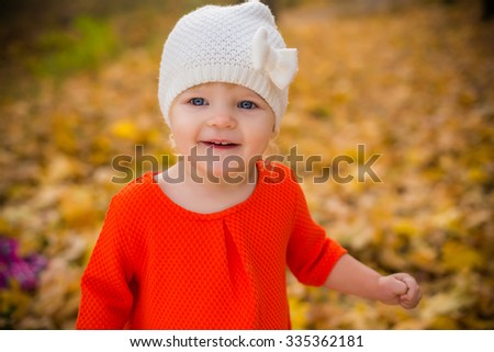 smiling baby in autumn forest with yellow leaves - stock photo