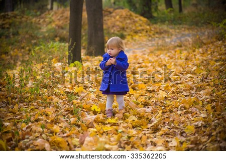 smiling baby in autumn forest with yellow leaves playing and getting cold