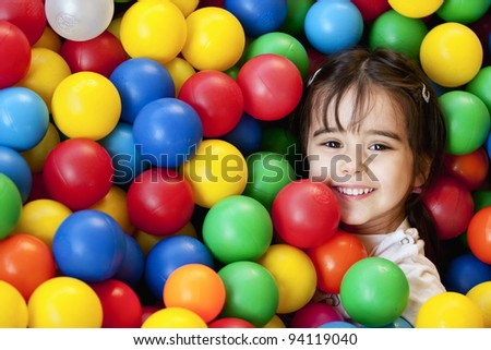 smiling baby in balls sea - stock photo