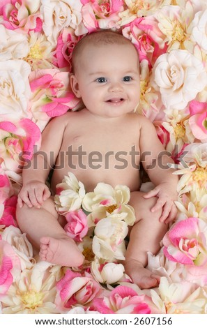 smiling baby in bed of flowers - stock photo