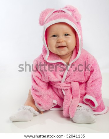 Smiling baby in pink bathrobe - stock photo