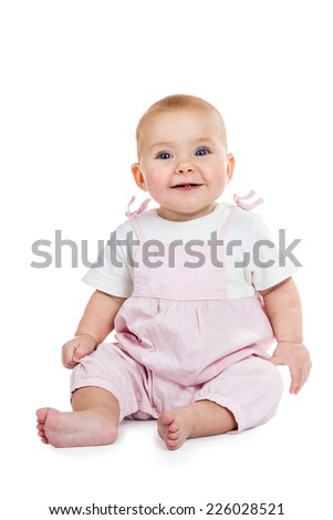 Smiling baby in pink jumpsuit sitting on the floor isolated on white background - stock photo