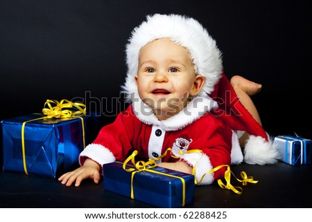Smiling Baby in Santa hat playing with Christmas box, isolated - stock photo