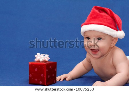 Smiling baby in santa's cap with gift - stock photo