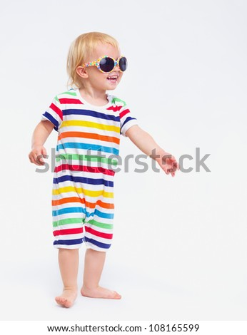 Smiling baby in swimsuit and sunglasses looking on copy space - stock photo