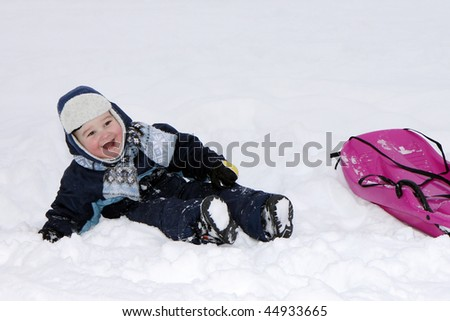 Smiling baby in winter with bobsleigh. - stock photo