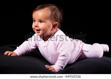 Smiling baby lies on black background