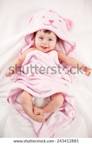 smiling baby looking at camera under a white blanket/towel  - stock photo