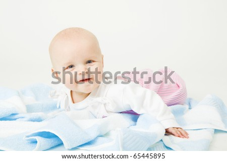Smiling baby lying on a blue towel. Studio photography