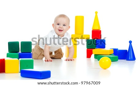 smiling baby playing among color building blocks - stock photo