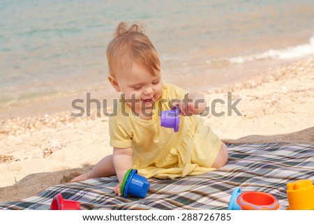 Smiling baby playing on the beach - stock photo