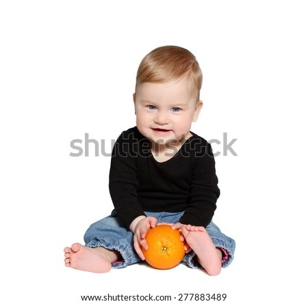 smiling baby sits and holds orange in hands on white background - stock photo