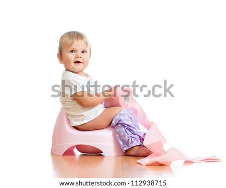 smiling baby sitting on chamber pot with toilet paper roll - stock photo