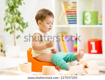 smiling baby sitting on chamber pot with toilet paper rolls - stock photo
