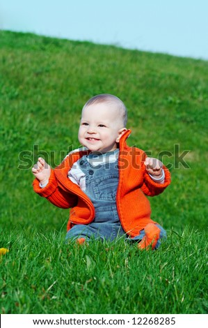 smiling baby sitting on green grass - stock photo