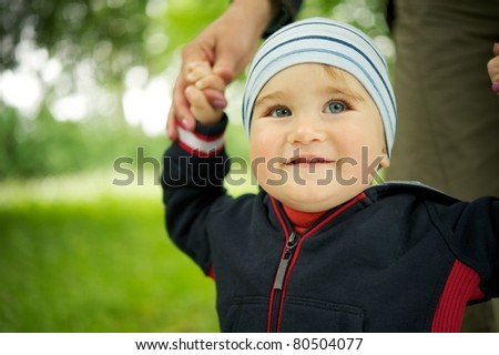 Smiling baby standing outdoors - stock photo