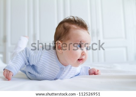 Smiling baby tummy time in a white nursery - stock photo