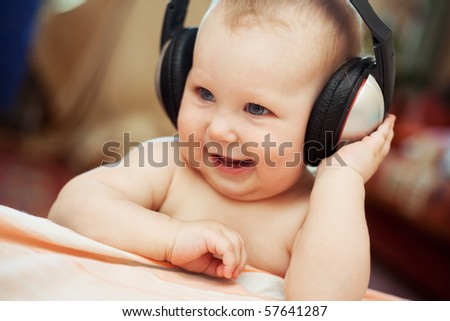 Smiling baby with headphone - stock photo