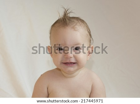 smiling baby with spiky hair, looking at camera with a neutral background - stock photo
