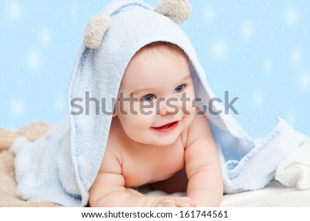 Smiling baby with towel on winter background - stock photo