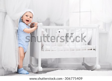 Smiling baby with toys on the carpet in my room - stock photo