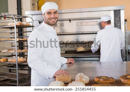 Smiling baker looking at camera in the kitchen of the bakery - stock photo