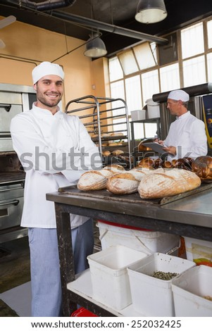 Smiling baker looking at camera with arms crossed in the kitchen of the bakery
