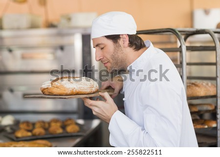 Smiling baker smelling fresh bread in the kitchen of the bakery - stock photo