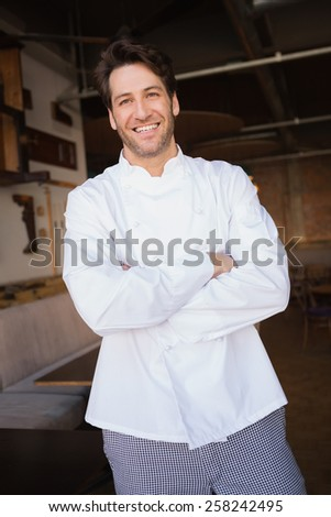 Smiling baker standing with arms crossed at the bakery - stock photo