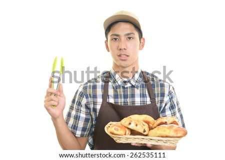 Smiling baker with breads - stock photo