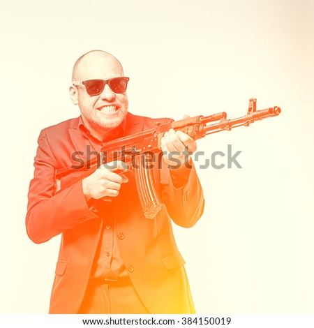 Smiling bald man in a gray suit and sunglasses holding a machine gun in his hands. Toned - stock photo
