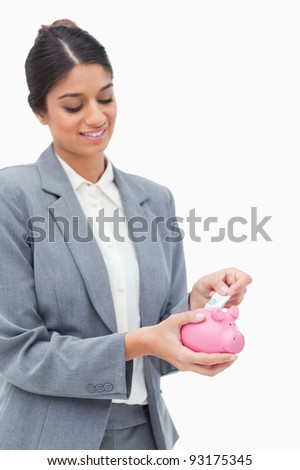 Smiling bank assistant putting bank note into piggy bank against a white background