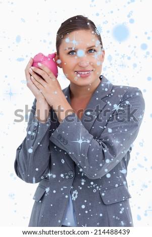 Smiling bank clerk shaking piggy bank against snow falling - stock photo
