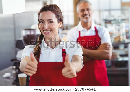 Smiling barista gesturing thumbs up with colleague behind at the cafe - stock photo