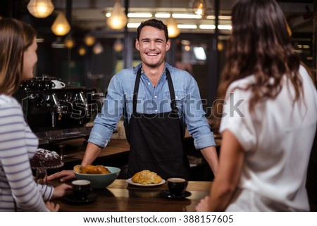 Smiling barista looking at the camera in the bar - stock photo