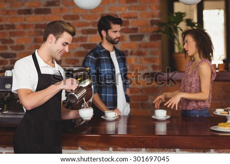 Smiling barista pouring milk into cup in front of customers at coffee shop - stock photo