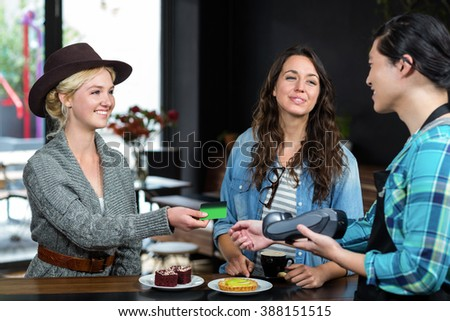 Smiling barista taking credit card from customer at the coffee shop - stock photo