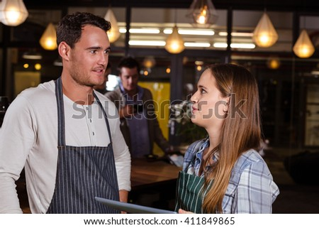 Smiling baristas talking while holding tablet in the bar